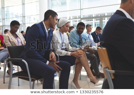 Side view of diverse business people discussing over digital tablet during seminar in office buildin Stock photo © wavebreak_media