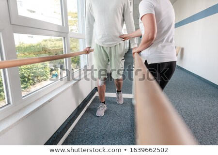 Therapist helping young man learning to walk again in rehabilitation Stock photo © Kzenon