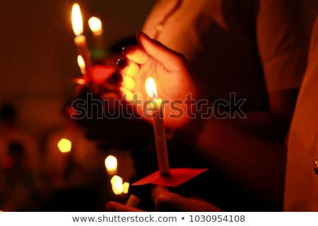 hands holding a candle on black background stock photo © andreykr
