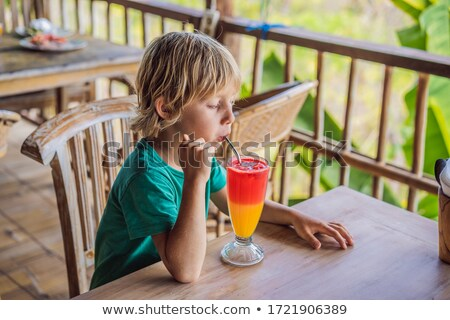 Boy drinks two tone cocktail in a glass in the cafe Stock photo © galitskaya