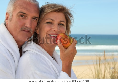 Mature couple in bathrobes eating an apple on the beach Stock photo © photography33