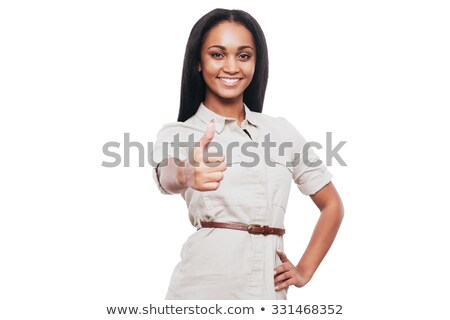 A young woman is standing with her hand on her hip and her thumb against a white background  Stock photo © wavebreak_media