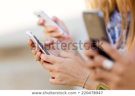 three girls chatting with their smartphones stock photo © nenetus