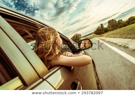 Smiling beautiful girl looks out of a car window stock photo © Kor