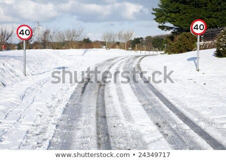snow tracks on a country road and 40 mph signs stock photo © latent