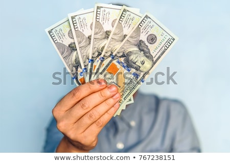 businessman counting hundred dollar bills stock photo © deandrobot