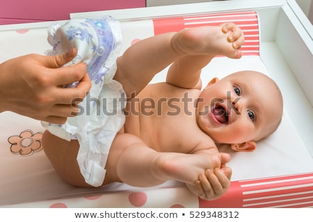 mother changes dirty diaper to little baby at home stock photo © diego_cervo