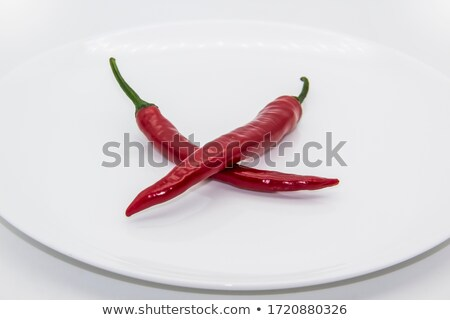 two red hot chilly peppers on plate isolated on white Stock photo © tetkoren