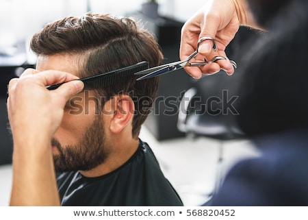 Modern barber combing hair of client with beard at barbershop Stock photo © deandrobot