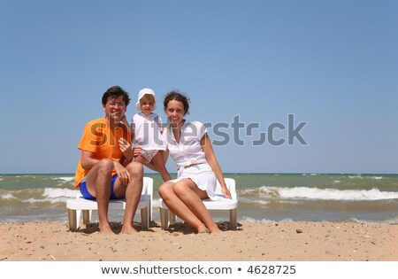 Mum, the daddy and the child sit on chairs near the sea. Stock photo © Paha_L