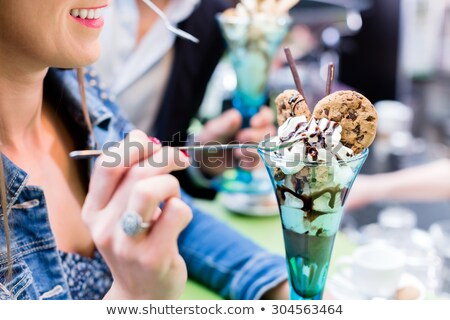 Woman eating an ice cream in a parlor or cafe Stock photo © dash