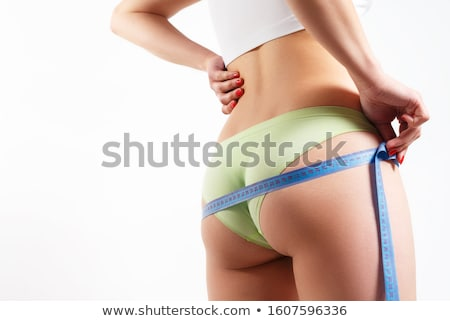 Slim woman measures her butt, isolated on a white background Stock photo © Nobilior