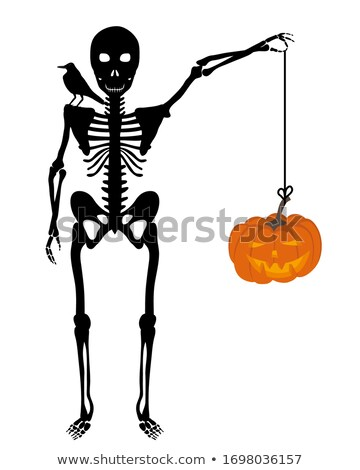 Creepy skull with black bird sitting on skeleton hand           Stock photo © Sandralise