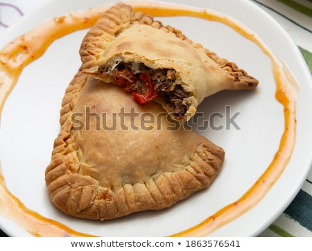 tasty pasties filled with meat and vegetables on board with red stock photo © yatsenko
