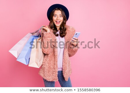 fashionable brunette girl in pink fur coat holding mobile phone stock photo © victoria_andreas