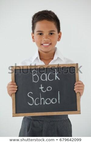 Iskolás fiú tart ír szöveg vissza az iskolába fehér Stock fotó © wavebreak_media