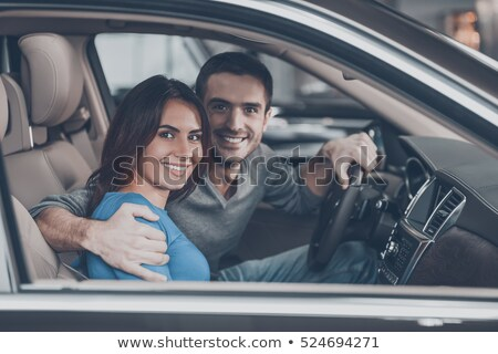 young smiling couple sitting at the front seats of their new car stock photo © deandrobot