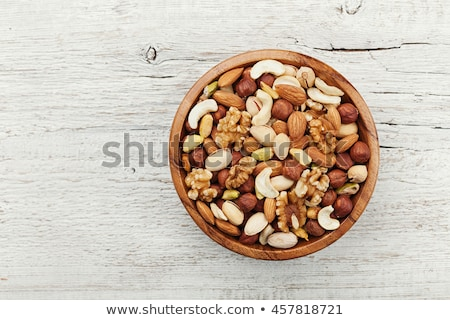 pistachio nuts on wooden background top view stock photo © yelenayemchuk