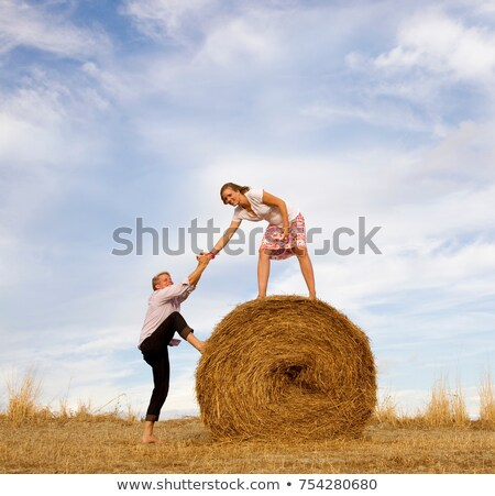 woman helping man to climb hay bale Stock photo © IS2
