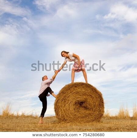 Stock photo: woman helping man to climb hay bale