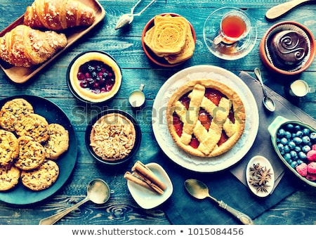 top view of a wood table full of cakes fruits coffee biscuits stock photo © davidarts