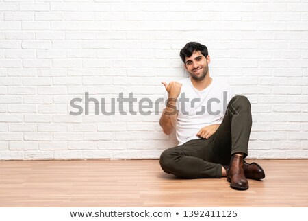 seated casual man pointing finger to side Stock photo © feedough