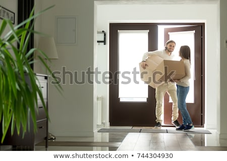 man with cardboard box opening door of new house Stock photo © LightFieldStudios