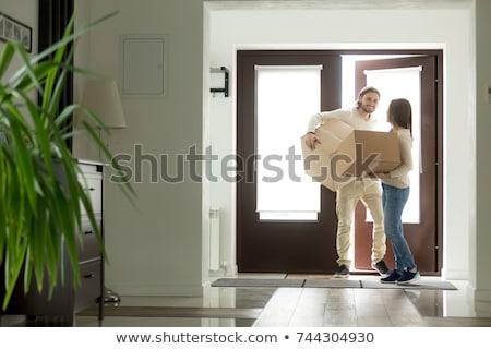 man with cardboard box opening door of new house Stock photo © LightFieldStudios