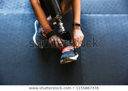 Strong disabled sports woman tie her laces in gym. Stock photo © deandrobot