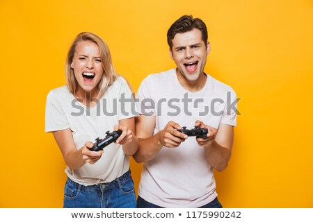 Young loving couple standing isolated over yellow wall background play games with joysticks. Stock photo © deandrobot