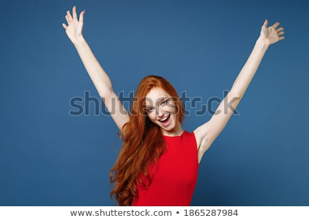 image of happy woman 20s wearing red dress laughing standing is stock photo © deandrobot