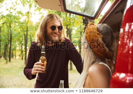 Photo of joyous hippie couple man and woman smiling, and drinkin Stock photo © deandrobot