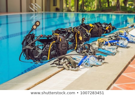 Stock photo: Equipment for diving is on the edge of the pool, ready for a lesson
