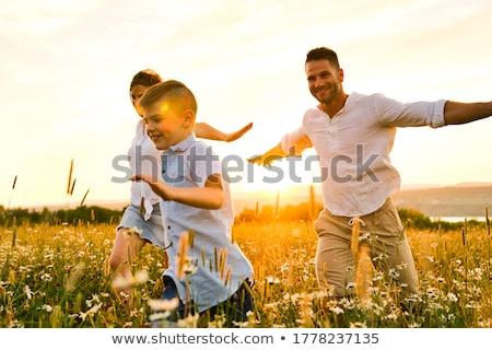 Famille heureuse Daisy domaine coucher du soleil famille Photo stock © Lopolo