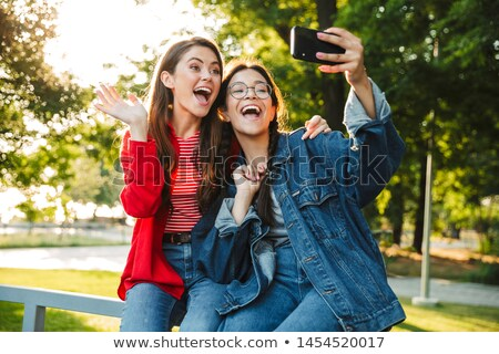two excited young girls students sitting on a grass stock photo © deandrobot