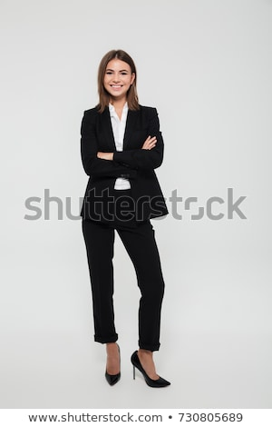 Confident elegant young businesswoman stands with crossed hands Stock photo © filipw