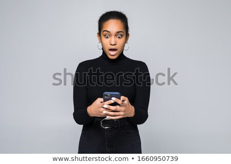 Shocked surprised woman posing isolated over grey wall background talking by mobile phone. Stock photo © deandrobot