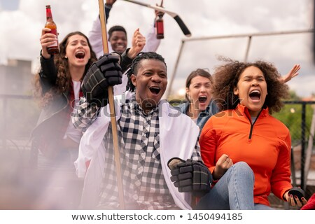 Mixed-race couple and their friends cheering for their favorite hockey team Stock photo © pressmaster