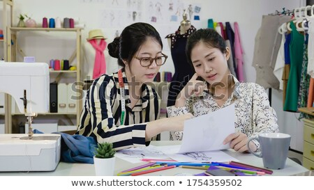 two young dressmaker or designer colleagues working and discussi stock photo © freedomz