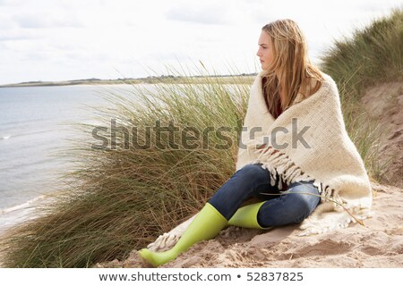 Young Woman Sitting In Sand Dunes Wrapped In Blanket stock photo © monkey_business