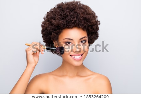 Beautiful young woman applying foundation on her face with a makeup brush isolated on gray backgroun Stock photo © serdechny