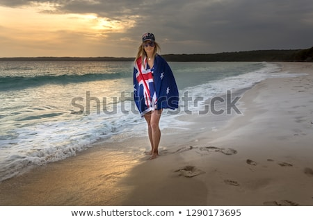 woman walking along the wet sand of the beach early morning stock photo © lovleah