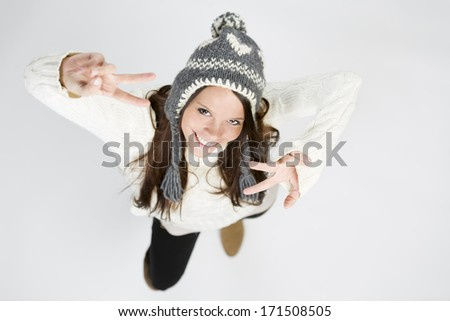 Sweet girl in cool winter clothing laughing, making victory sign Stock photo © lichtmeister