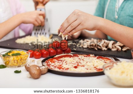 Young hands prepare pizza at home - grate and sprinkle the chees Stock photo © ilona75