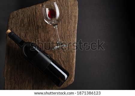Elegant glass of red wine with dark grapes on wooden board on black background. Space for text Stock photo © DenisMArt