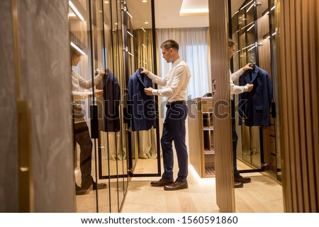Young man choosing clothes from  wardrobe in the hall of contemp Stock photo © boggy