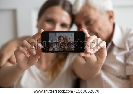happy young woman with smartphone embracing senior father while making selfie stock photo © pressmaster