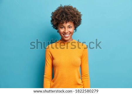 Half length shot of cheerful Afro American woman with dark bushy hairstyle, wears violet suit, point Stock photo © vkstudio