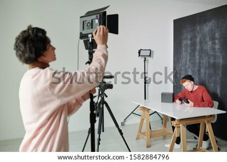 Moço filmadora tiroteio estúdio em pé masculino Foto stock © pressmaster