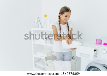 Small adorable busy girl stands in laundry basket, pours detergent in washing machine compartment, h Stock photo © vkstudio